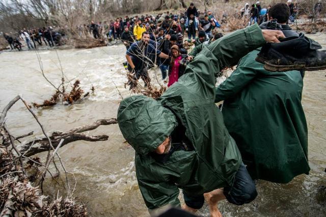 Idomeni, 2016. március 15. Migránsok átkelnek egy folyón a görögországi Idomeni és a macedóniai Gevgelija között 2016. március 14-én. MTI Fotó: Balogh Zoltán